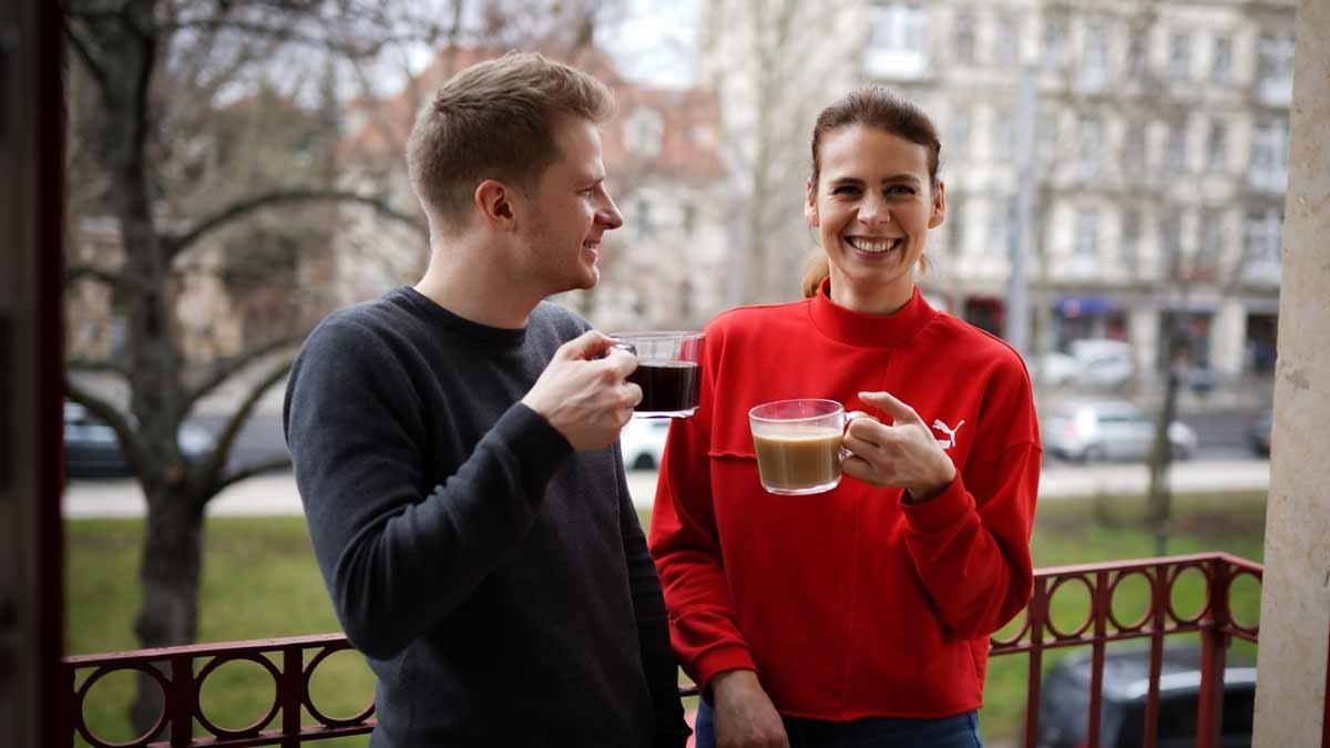 Jenny und Maxi von Die Berater trinken Kaffee auf dem Balkon