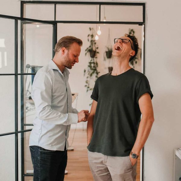 2 Mitarbeiter von Die Berater Online Marketing haben Spaß bei der Arbeit